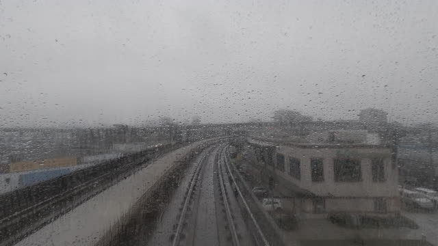view from a windshield covered with raindrops of a moving city electric train - richmond columbia britannica video stock e b–roll