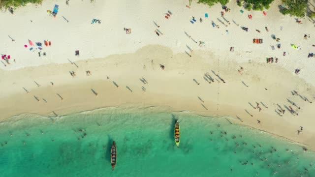 utsikt från ovan, flyg utsikt över en vacker tropisk strand med vit sand och turkos klart vatten, longtail båtar och människor sola, freedom beach, phuket, thailand. - provinsen phuket bildbanksvideor och videomaterial från bakom kulisserna