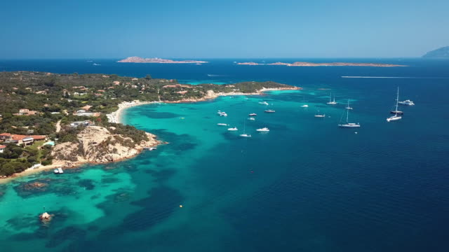 view from above, aerial view of a transparent and turquoise sea with some boats and yachts in front a beautiful beach. emerald coast, sardinia, italy. - sardegna video stock e b–roll