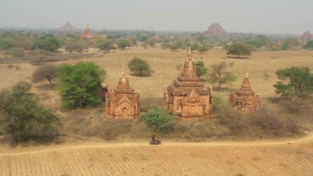 上からの眺め、バガンの考古学地帯の e バイクを運転する未確認の観光客の空中眺め。古代仏教寺院の何百もの素晴らしい風景。バガン, ミャンマー. - 仏塔点の映像素材/bロール