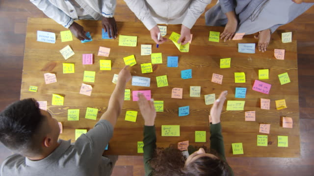 View from Above of Creative Business Team Working with Sticky Notes Top view of creative team of multi-ethnic coworkers sharing sticky notes and putting them on wooden table while brainstorming in the office brainstorming stock videos & royalty-free footage