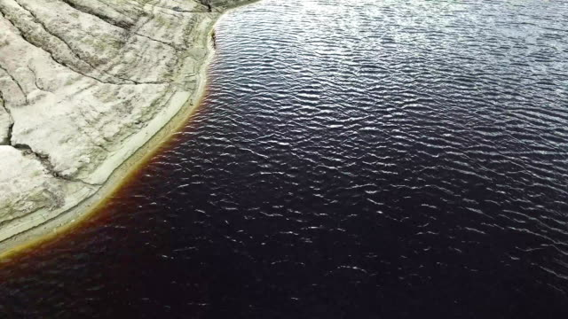 View from above of island in the beautiful blue lake. Footage. Top view of the lake shore in autumn video