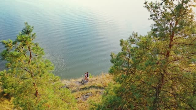 Bидео View from above on a young couple having time together near the calm water.