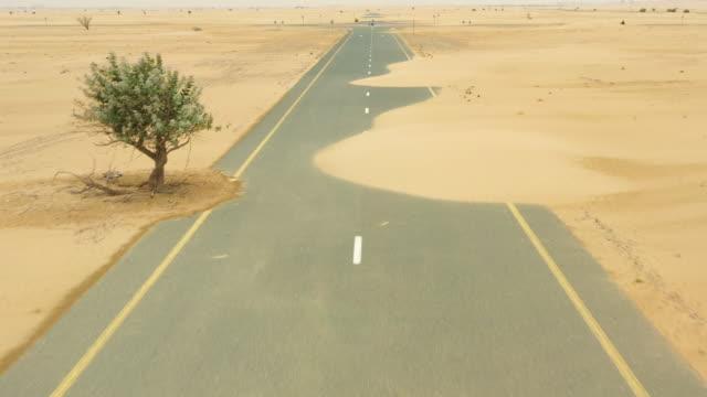 vidéos et rushes de vue d'en haut, vue aérienne imprenable sur une route déserte couverte de dunes de sable au milieu du désert de dubaï. dubaï, émirats arabes unis. - paysage extrême