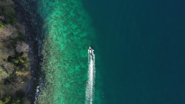 上からの眺め、ターコイズブルーの澄んだ海を航海する観光客とロングテールボートの素晴らしい空中写真。タイ、マヤ湾のピピ諸島。 - サムイ島点の映像素材/bロール