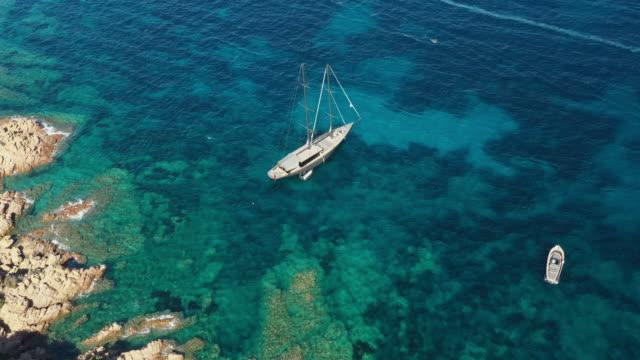 vídeos de stock, filmes e b-roll de vista de acima, vista aérea impressionante de um sailboat luxuoso que flutua em um mar desobstruído de turquesa bonito que banhe as costas verdes e rochosas de sardinia. costa esmeralda (costa smeralda) italy. - esmeralda