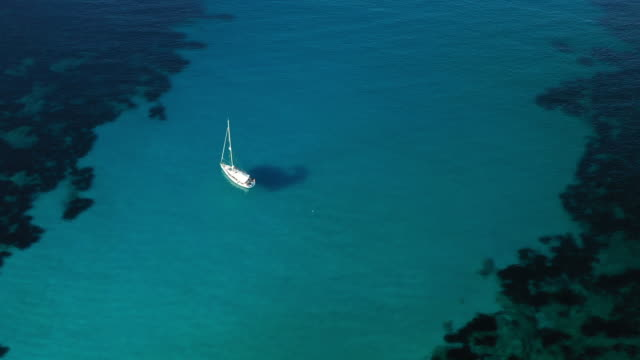 vídeos de stock, filmes e b-roll de vista de acima, vista aérea impressionante de um barco de navigação que flutua em um mar desobstruído de turquesa bonito. parque nacional do arquipélago de maddalena, sardinia, italy. - esmeralda