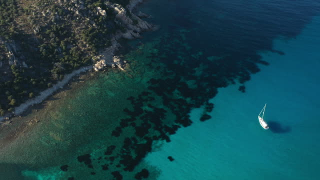 vídeos de stock e filmes b-roll de view from above, stunning aerial view of a sailing boat floating on a beautiful turquoise clear sea. maddalena archipelago national park, sardinia, italy. - arquipélago