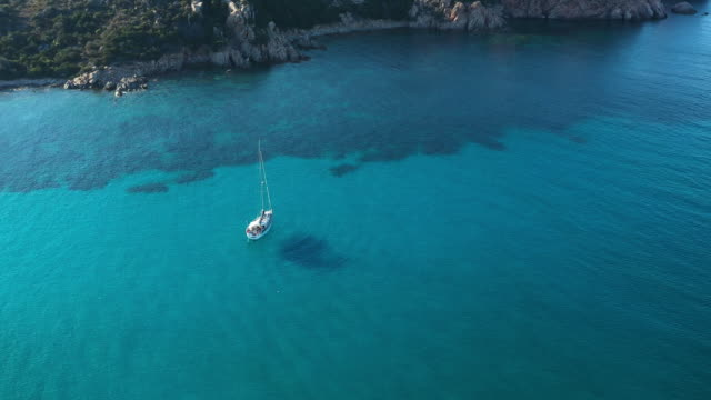 vídeos de stock e filmes b-roll de view from above, stunning aerial view of a sailing boat floating on a beautiful turquoise clear sea. maddalena archipelago national park, sardinia, italy. - ibiza
