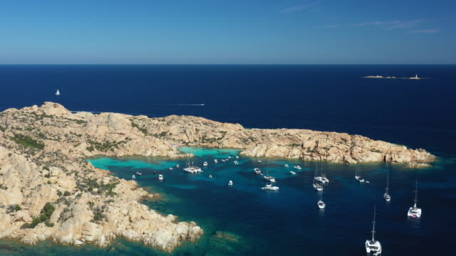 vídeos de stock e filmes b-roll de view from above, stunning aerial view of cala coticcio also known as tahiti with its rocky coasts and small beaches bathed by a turquoise clear water. la maddalena archipelago, sardinia, italy. - arquipélago