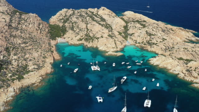 view from above, stunning aerial view of cala coticcio also known as tahiti with its rocky coasts and small beaches bathed by a turquoise clear water. la maddalena archipelago, sardinia, italy. - sardegna video stock e b–roll