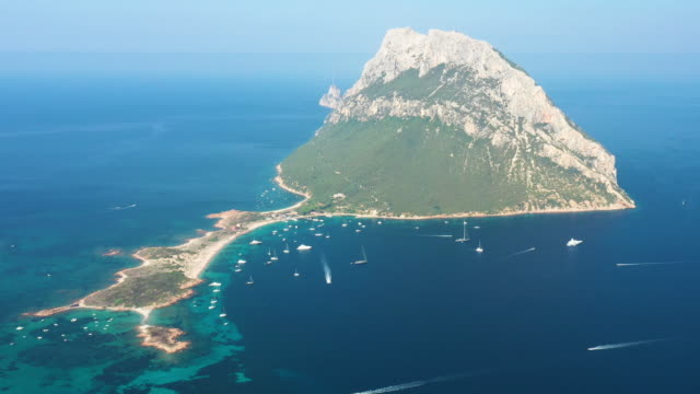 view from above, stunning aerial view of the beautiful tavolara island with its beach bathed by a turquoise clear sea. tavolara is a small island off the northeast coast of sardinia, italy. - sardegna video stock e b–roll