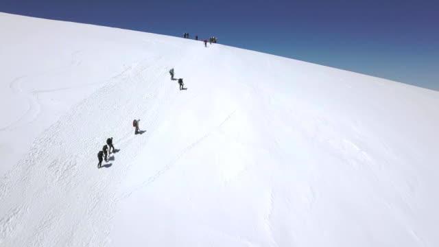 View from above tourist group walking on snow mountain trail. Winter mountains video