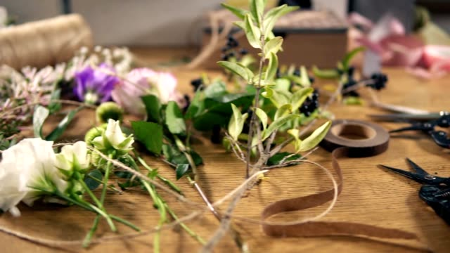 View from above: wooden table with flowers, scissors, tapes, decorating paper and other tools for bouquet's arrangement at flower shop. Slowmotion shot video