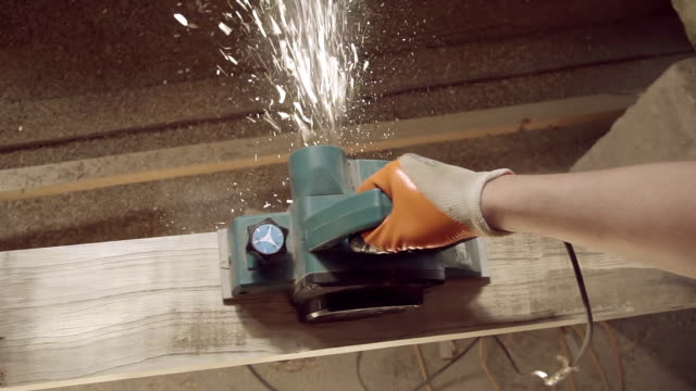 View from above Work carpenter in the workshop. Electric Planer. Treatment of wooden planks electric tool in slow motion video
