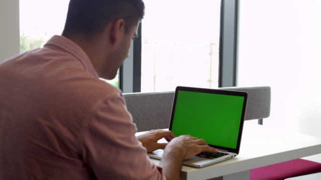 view from behind of male student using laptop shot on r3d - solo un uomo giovane video stock e b–roll