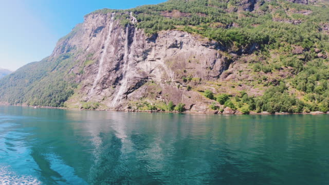 view from boat of seven sisters waterfall and green fjord in geiranger - fiordo video stock e b–roll