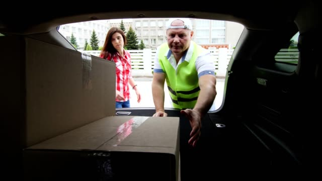 View from car trunk: Couriers, man and woman, unloading parcels, cardboard boxes from car trunk. Cargo delivery service - vídeo