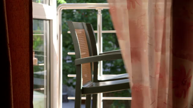 からの眺めホテルのお部屋の窓を通してオープンのガラスドアからバルコニーに手を振るカーテン - デッキ点の映像素材/bロール