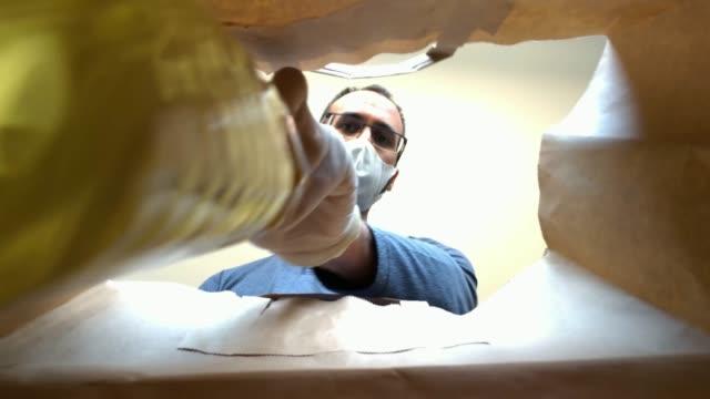 utsikt inifrån en papperspåse med en man med mask och handskar fyllning mat - välgörenhet bildbanksvideor och videomaterial från bakom kulisserna