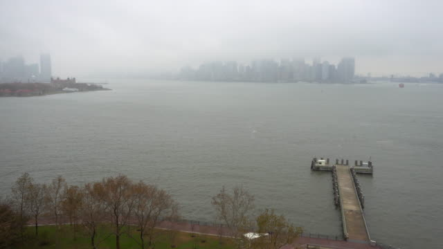 New York, New York / USA - November 18, 2019 : View from Liberty island. New york city cityscape in fog cold day
