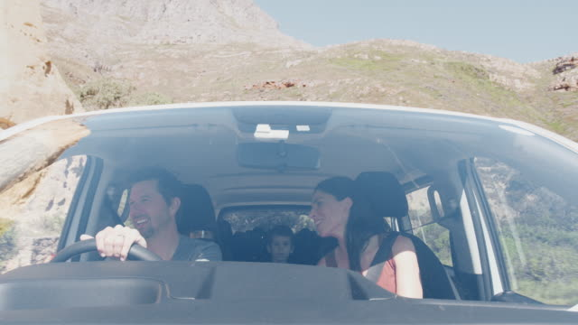 View From Outside Vehicle As Family Drive Car Along Mountain Road To Vacation Destination