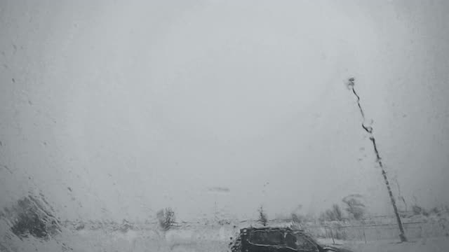 View from parked car to the highway under the snowfall