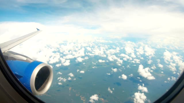 view from porthole of flying airplane wing with turbine under island Sri-Lanka among white clouds