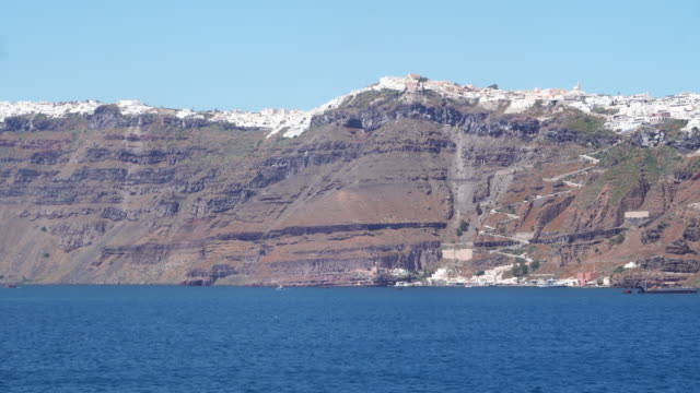 view from sea to santorini caldera and iconic architecture of fira town - isole egee video stock e b–roll