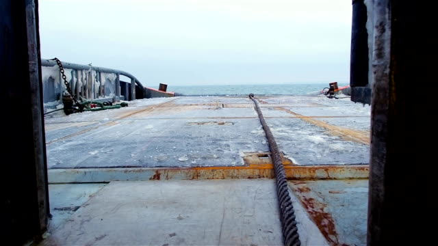 View from ship deck floor with line on it on ice covered board and calm sea