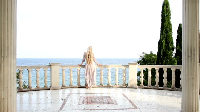 view from the back of a woman who stands on an ancient terrace by the sea - balaustrata video stock e b–roll