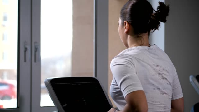 view from the back. the girl runs on a treadmill, looks out the window. 4k slow mo - runner rehab gym video stock e b–roll