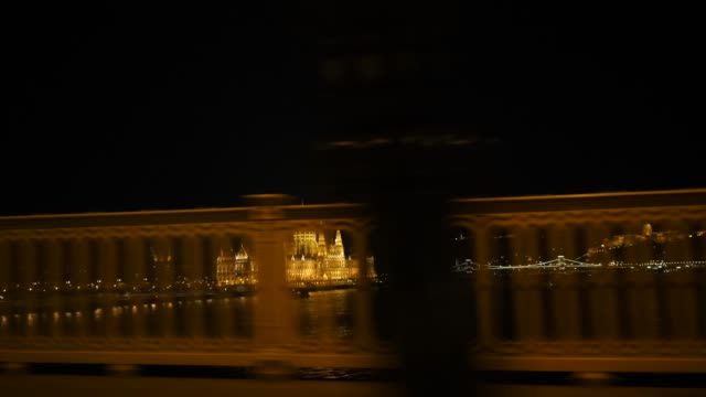 View from the car from the chain bridge View from the car from the chain bridge to the cathedral in Budapest. Night shooting, clear sky, a fence in the foreground flashes and architectural buildings in yellow illumination. hungary stock videos & royalty-free footage