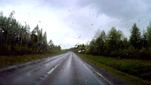 View from the car in the rain driving on wet roads. Driving a Car on a Road in Norway video