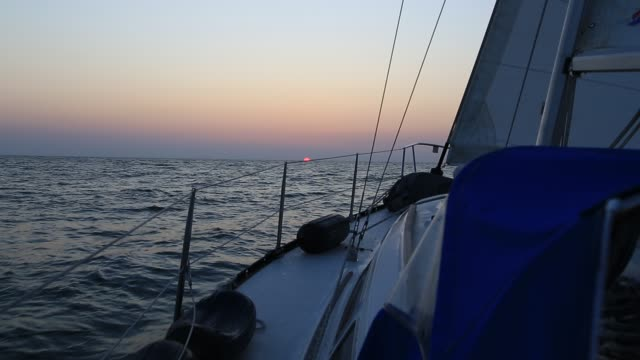View from the deck of a sailboat, rigging and foresail silhouetted against a brilliant sunset or sunrise sky
