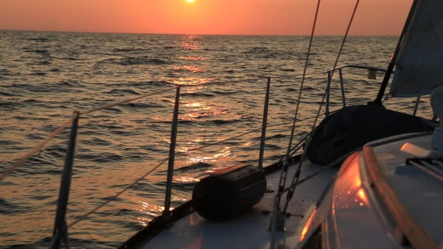View from the deck of a sailboat, rigging and foresail silhouetted against a brilliant sunset or sunrise sky video