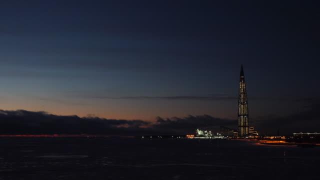 夜空に照らされた夜光に照らされたガスプロムタワーのフィンランド湾からの眺め。概念。超高層ビル「ラフタセンター」ガスプロム本社夜景 ビデオ