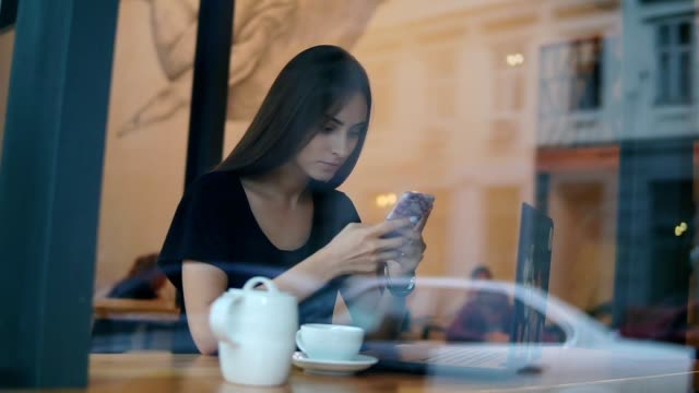 View from the outside of a concentrated young lady with long hair and natural makeup using her mobile phone in the coffee shop. White cup with saucer and teapot on the wooden table