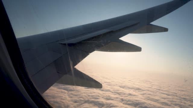 平面ウィンドウからのビュー。飛行機の窓の翼と空 - 旅行代理店点の映像素材/bロール