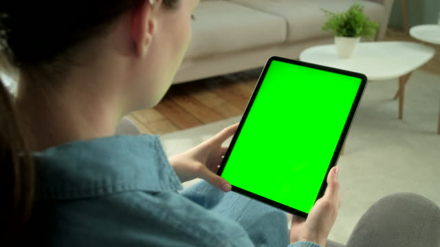 View From the Shoulder of Woman Using Hand Gestures on Green Mock-up Screen Digital Tablet Computer in Vertical Mode while Sitting on a Chair. In the Background Cozy Living Room View From the Shoulder of Woman Holding and Using Hand Gestures on Green Mock-up Screen Digital Tablet Computer Sitting on a Chair. Girl Buying stuff or Browsing Through the Internet. In the Background Cozy Living Room. ipad stock videos & royalty-free footage