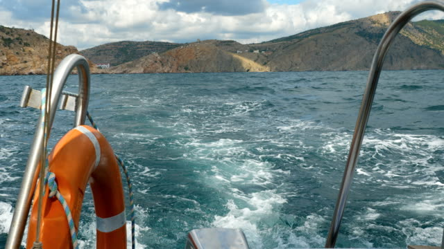 View from the side of a motor boat on the sea and mountains. View from the side of a motor boat on the sea and mountains. The boat swings on the waves. recreational boat stock videos & royalty-free footage