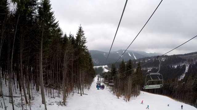 View from the ski lift. Ski lift and ski trail with skiers. video