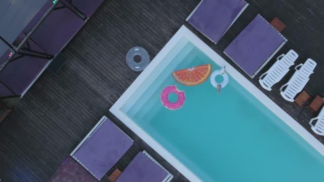 visa från toppen av poolen med ljusa färgade uppblåsbara cirklar. en ovanifrån av med mångfärgade uppblåsbara ringar och solen chairses stående vid poolen. skytte från drönaren. - inflatable ring bildbanksvideor och videomaterial från bakom kulisserna