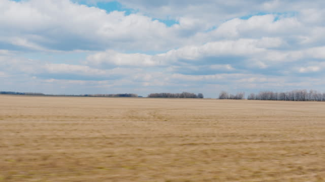 View from the window of a fast-moving car. Field early spring - plowed land and blue sky with clouds. Agricultural land. POV 3 axis stabilized video video
