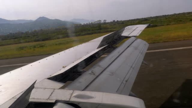 View from the Window on the Wing of an Airplane moving along the Runway at Airport after Landing View from the Window on the Wing of an Airplane moving along the Runway at Airport after Landing. Work flap and airbrake on the wing. landing touching down stock videos & royalty-free footage