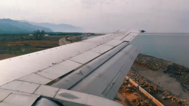 view from the window on the wing of an airplane moving along the runway at airport after landing - battere le ali video stock e b–roll