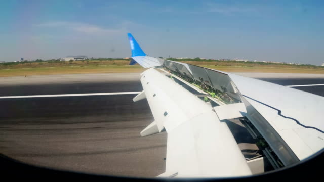 view from the window on the wing of an airplane moving along the runway at bangkok airport - battere le ali video stock e b–roll