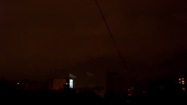 view from the window to the stormy sky. night outside, outside the window dressed with rains and lightning flashed. seen from the window high houses FullHD video