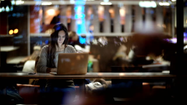 View inside the window on beautiful woman using the laptop in evening. Female closing the computer and leaving the cafe