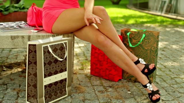 vídeos de stock, filmes e b-roll de exibir as pernas.  mulher compras. - saia